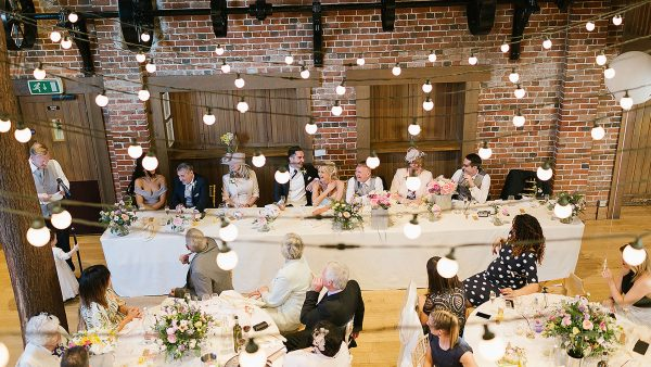 A wedding party enjoy the wedding speeches inside the stunning Mill Barn with exposed oak beams