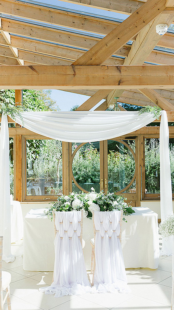 Beautiful white drapes and chair covers decorate the Orangery of this civil wedding venue in Essex
