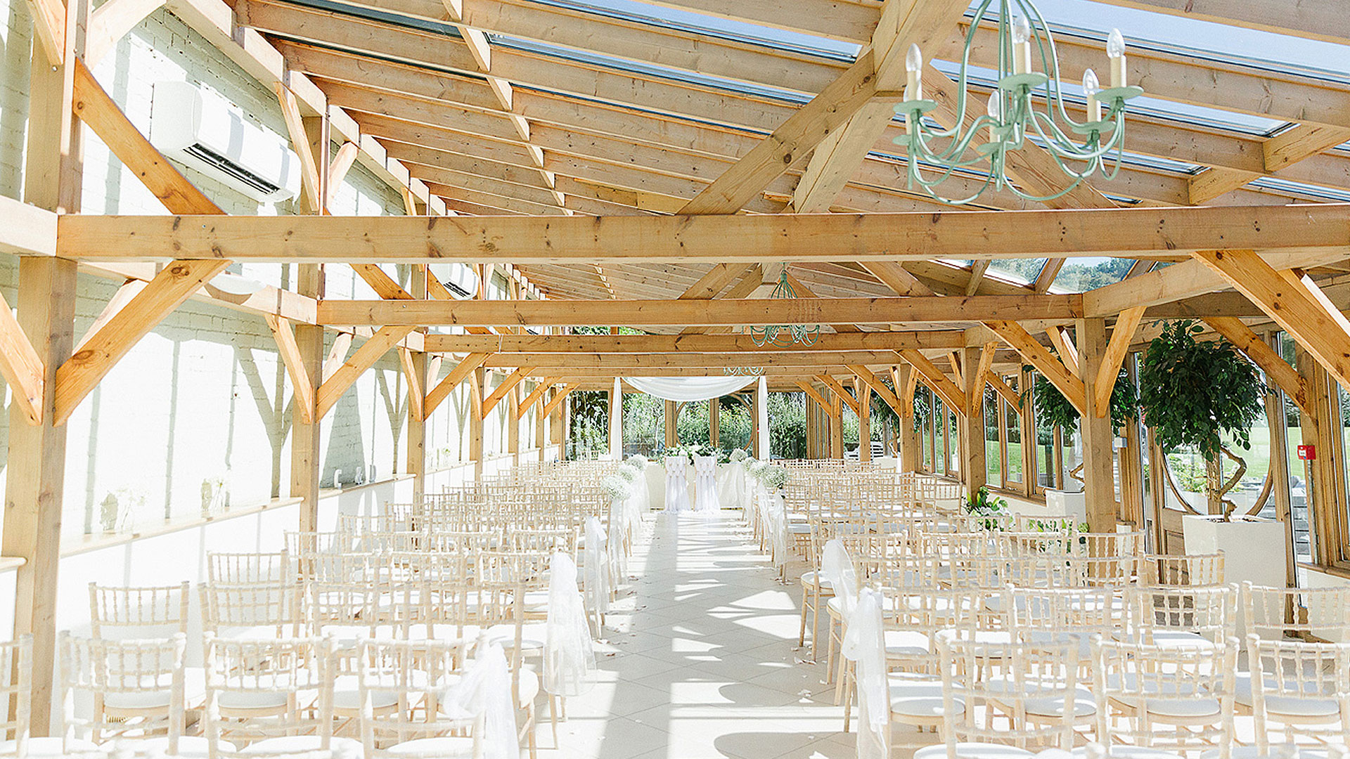 Rows of white wooden chairs line the Orangery ready for a beautiful and unique wedding ceremony