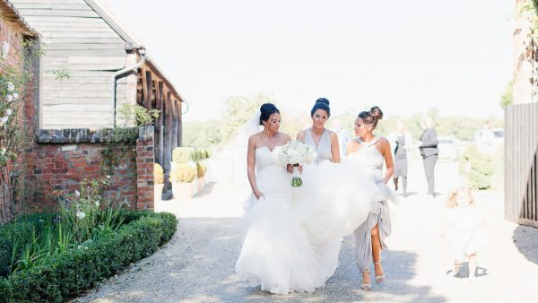 A bride and her bridesmaids make their way from the Gather Barn for more wedding photos