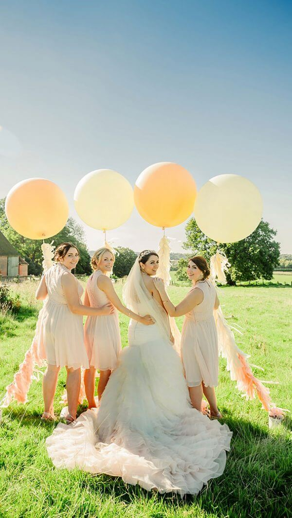 A bride and her bridesmaids enjoy the countryside setting with wedding balloons