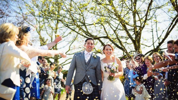 Be inspired with spring wedding ideas gaynes park essex a bride and groom are congratulated with confetti after their wedding ceremony junglespirit