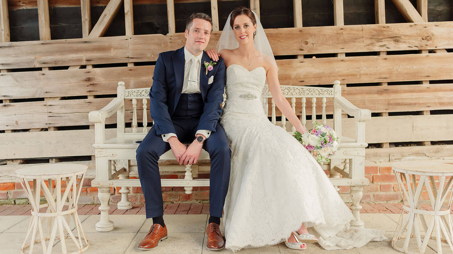 A bride and groom steal a moment on a white wedding bench - barn weddings Essex