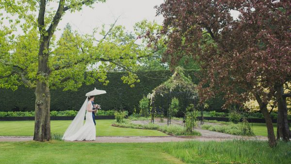 A bride walks down the long outdoor wedding aisle at one of the finest wedding venues in Essex