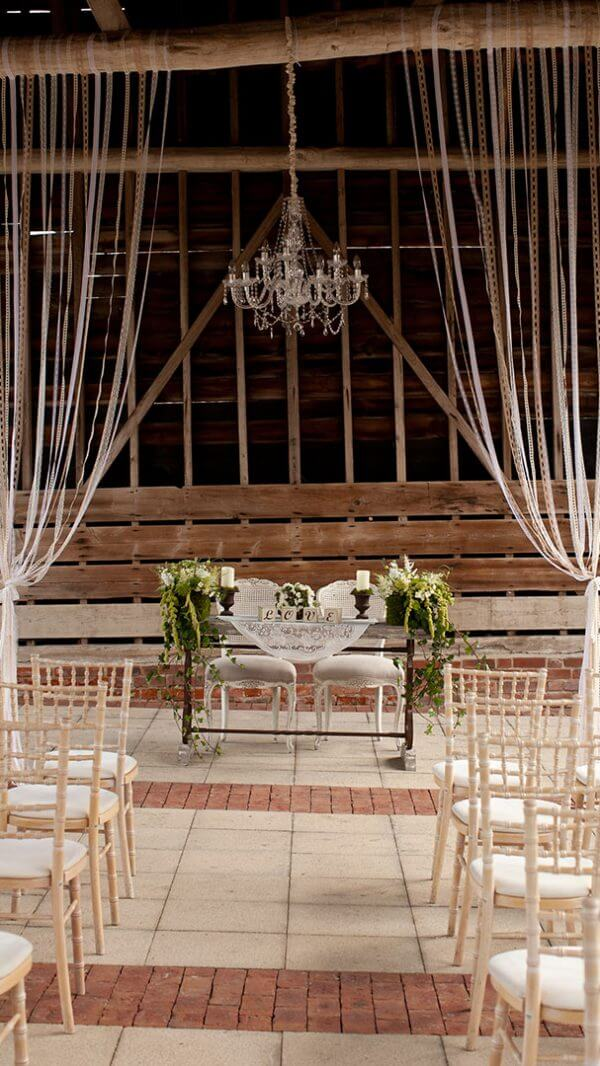 Beautiful green and white wedding flowers decorate the ceremony table of this outdoor wedding ceremony