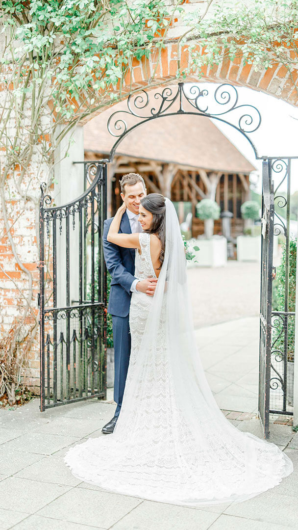 A happy couple embrace as they stand by an iron gate leading to the Gather Barn - Essex wedding venues