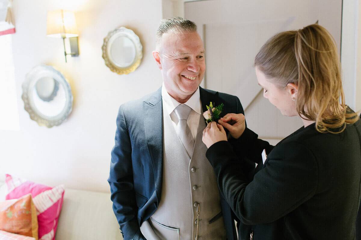 A wedding coordinator helps the father of the bride fix his wedding buttonhole – guest accommodation Essex