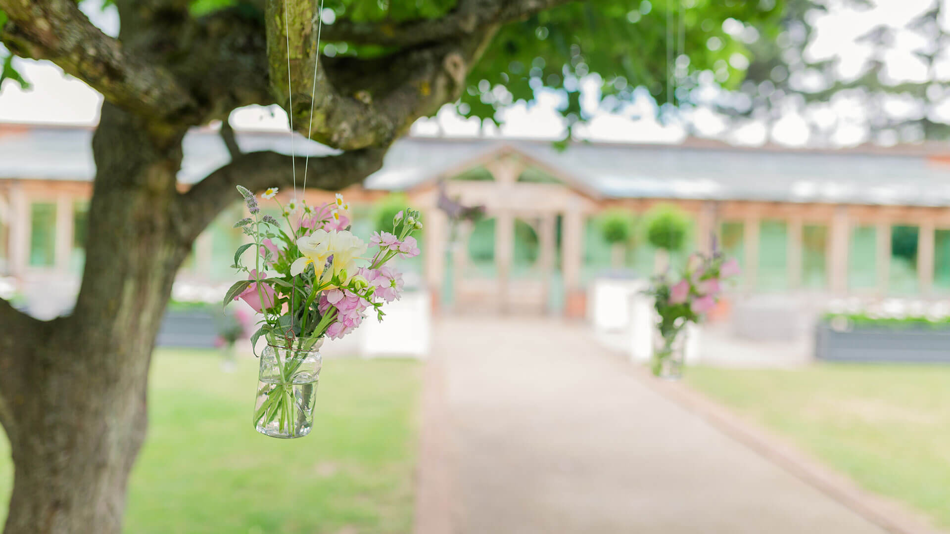 Flowers hang from glass jars in the Walled Garden for a summer wedding - summer wedding ideas