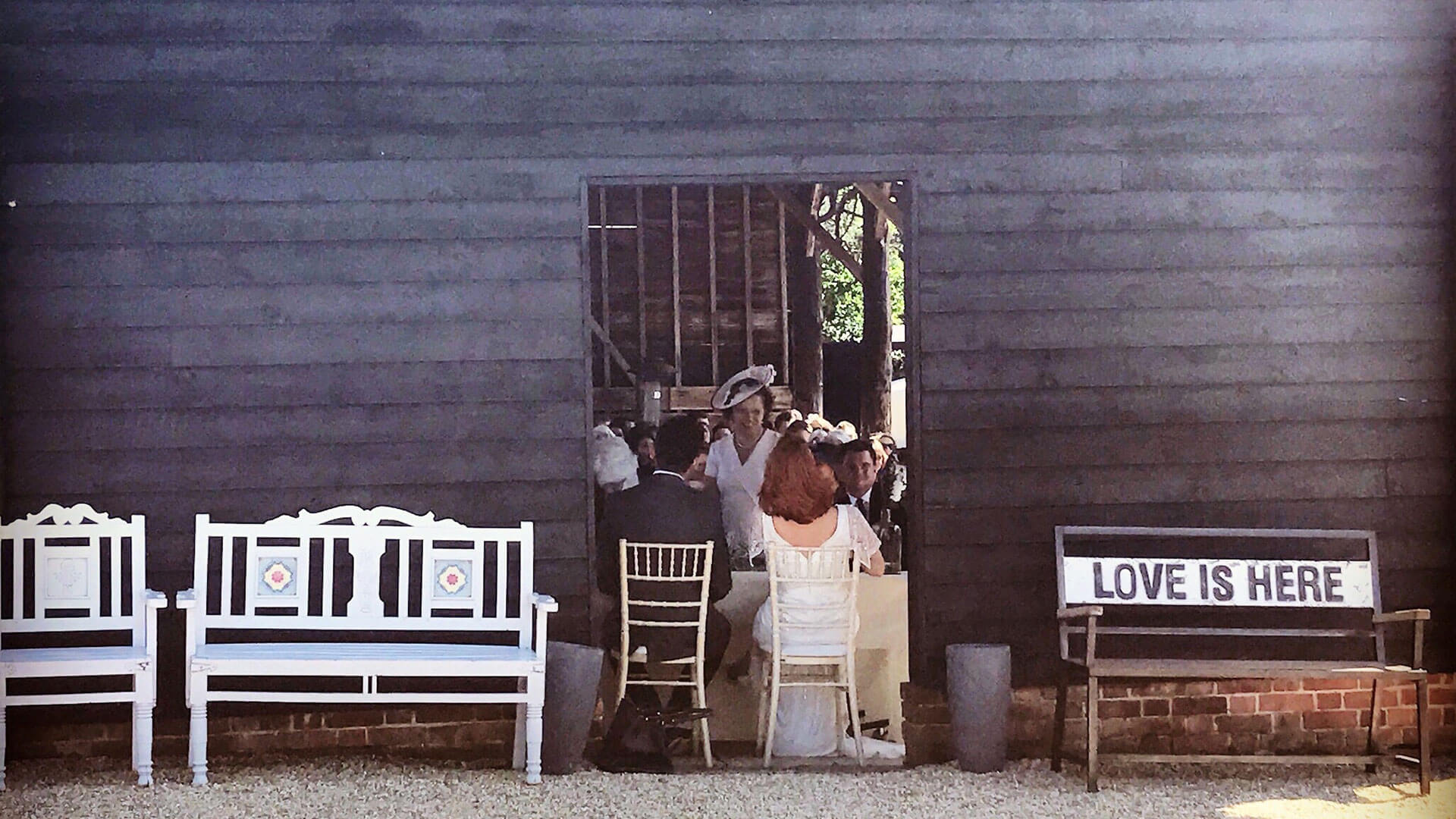 A bride and groom chat to guests in the open-sided Gather Barn - outdoor wedding venues in Essex