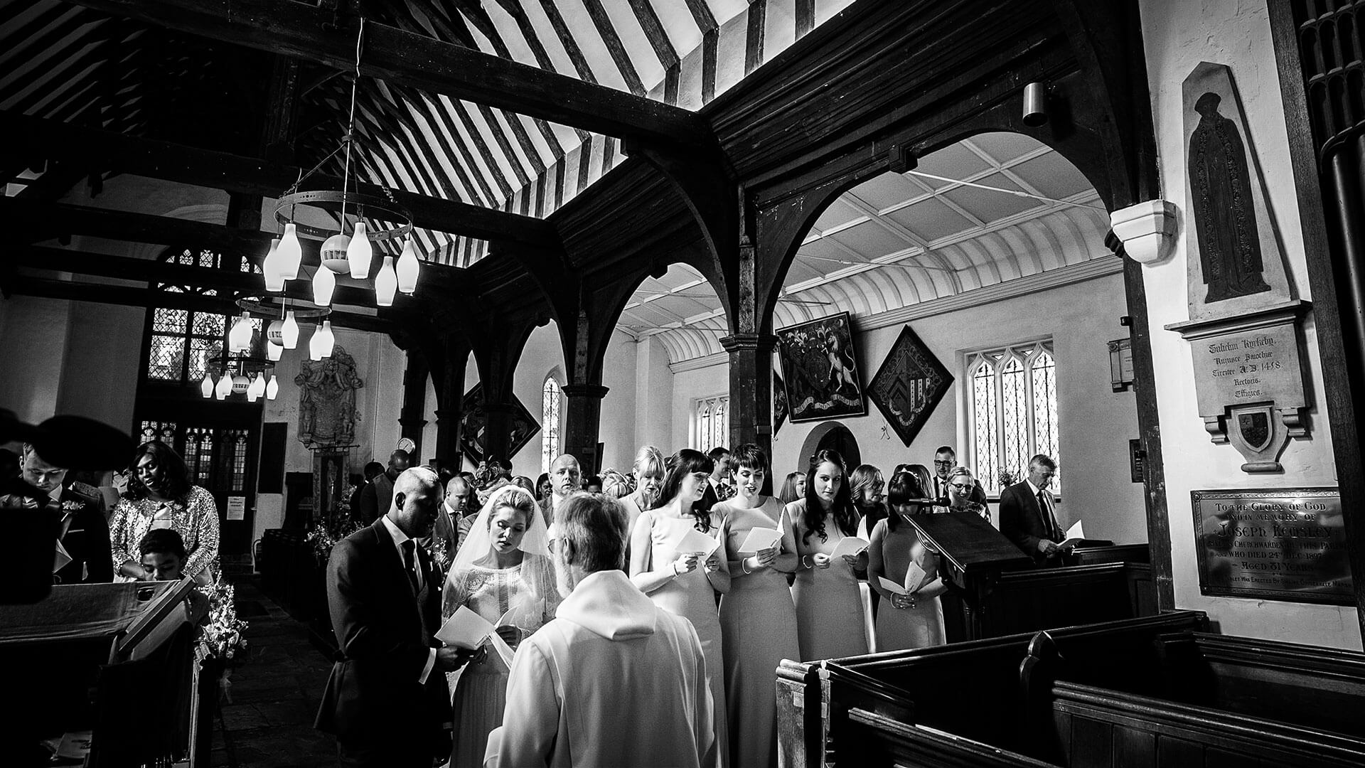 A wedding party sings hymns during their church wedding - wedding barns Essex