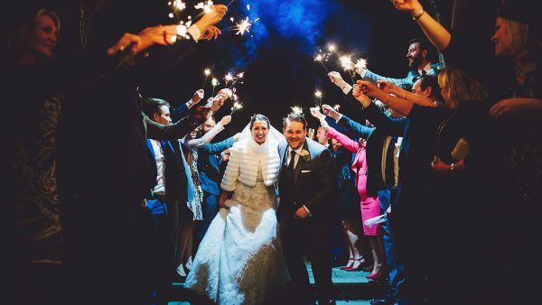 A happy couple are congratulated with sparklers at night - winter wedding ideas