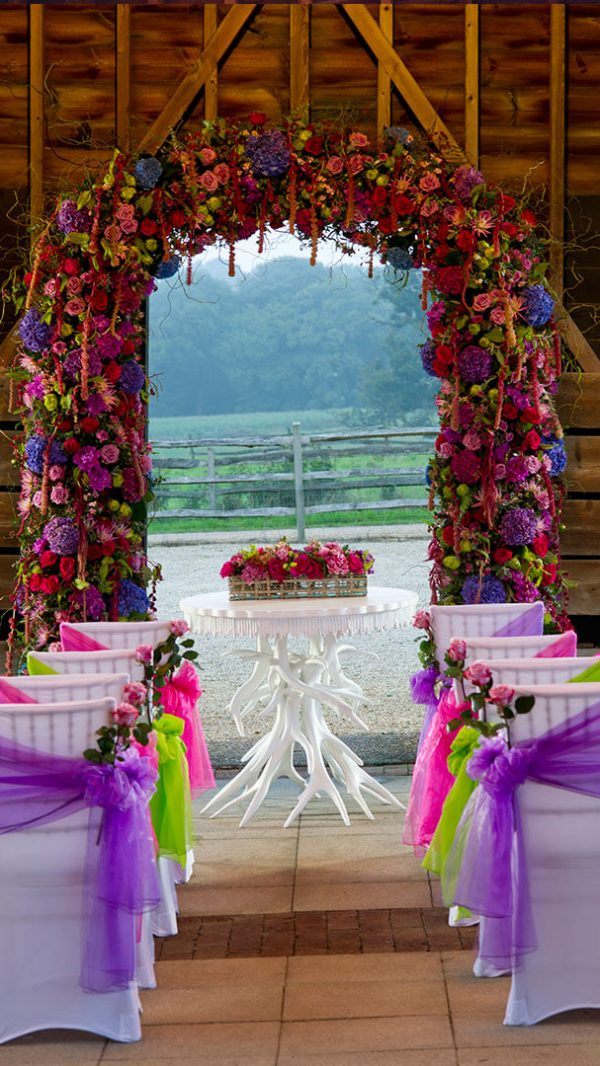 The open-sided Gather Barn is the perfect space for an outdoor wedding - decorated here with purple flowers