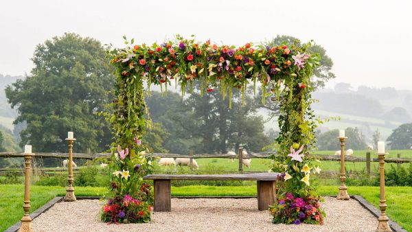A stunning wedding arch with purple flowers stands in the stunning grounds of this Essex barn wedding venue