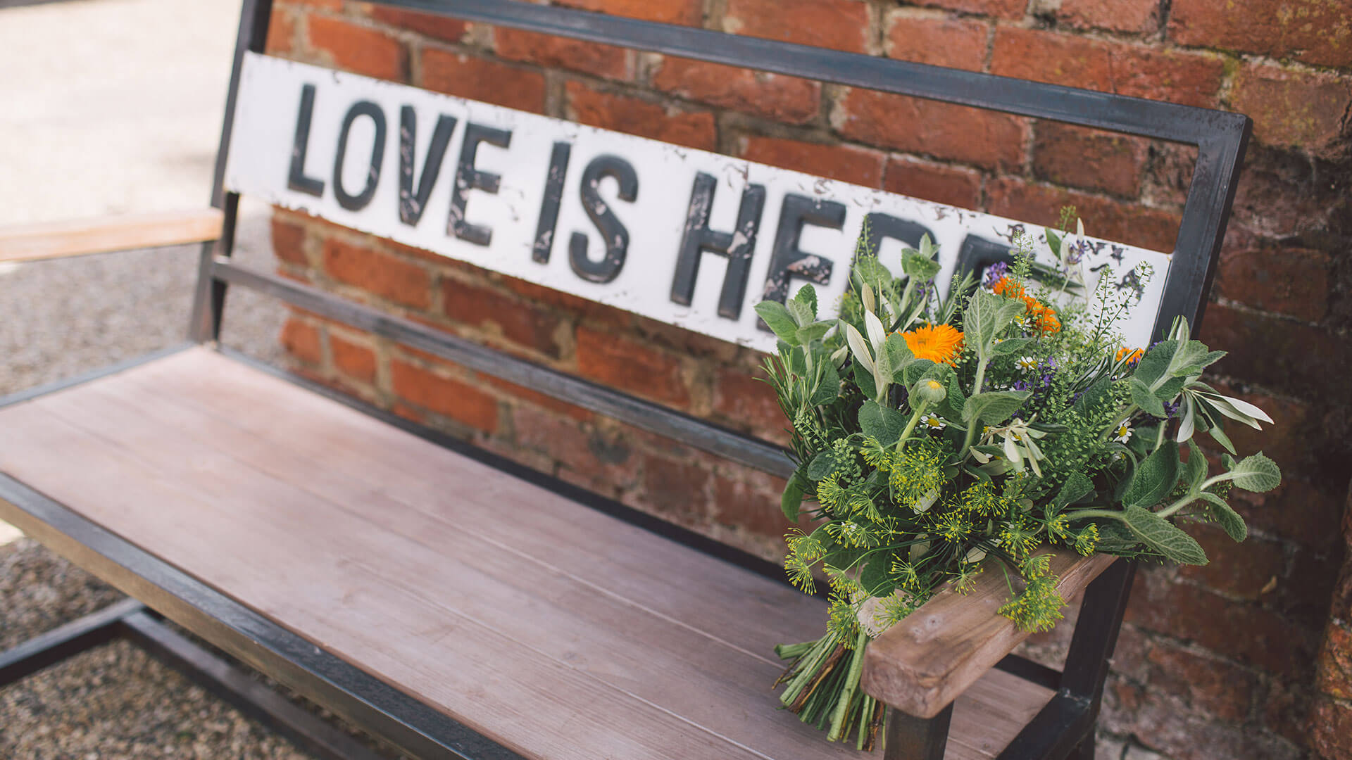 Pretty summer wedding flowers or green and yellow are placed on a bench that reads love is here