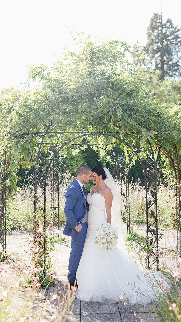 A happy couple steal secret moments in the beautiful gardens - barn wedding venues Essex