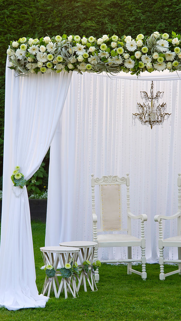 White drapes and a floral wedding arch provide a stunning structure for a blessing in the Walled Garden - wedding venues in Essex