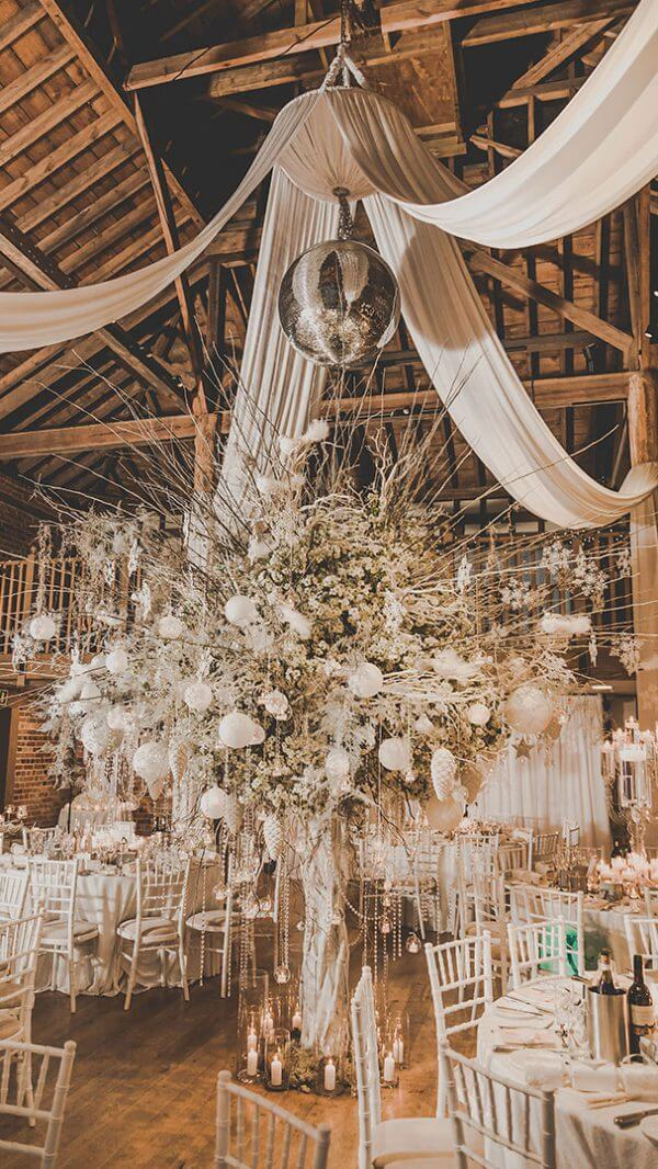 A huge centrepiece of branches baubles and candles creates a wow factor at this winter wedding