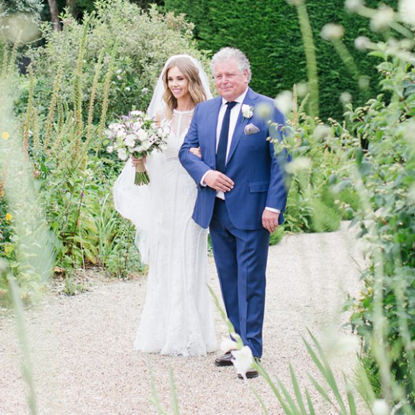 Bride and her father walking down the Long Walk towards the aisle at a Gaynes Park wedding