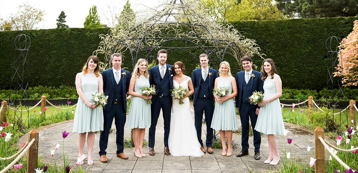 Bride and groom with their bridesmaids and groomsmen in the gardens of Gaynes Park