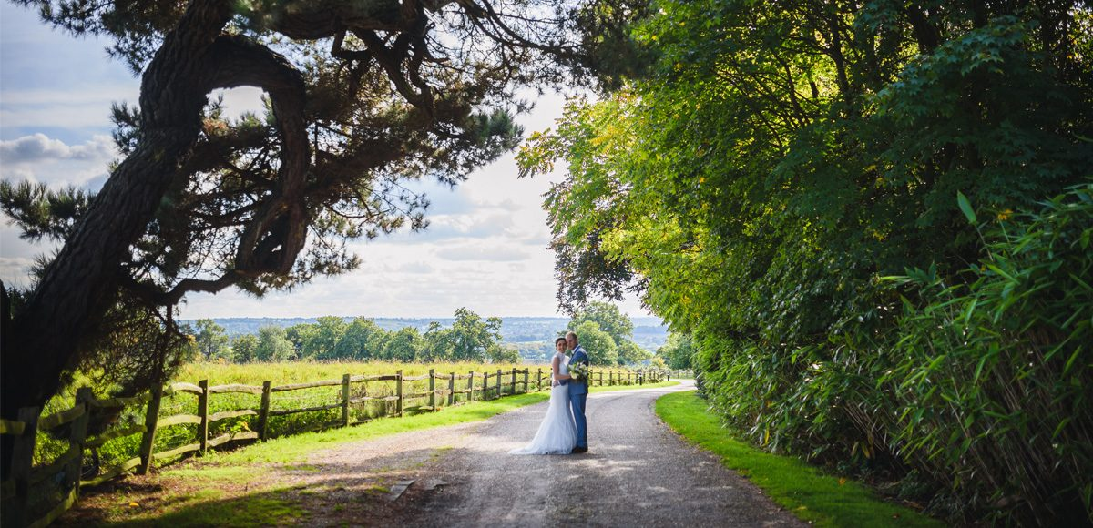 Bride and groom use the countryside views at Gaynes Park to take their wedding photos