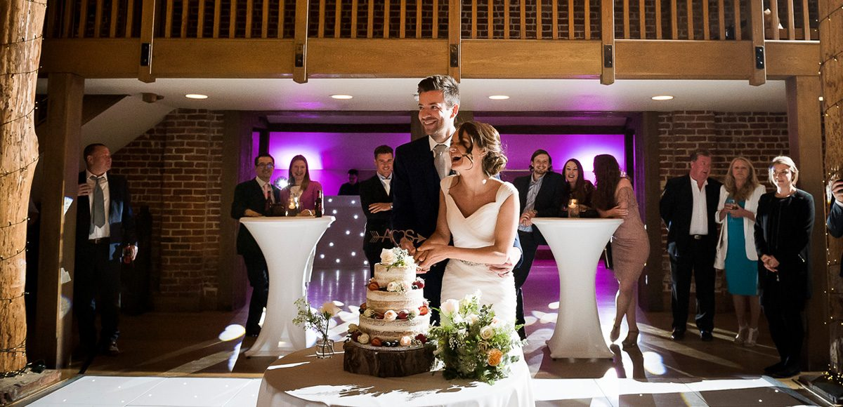Bride and groom cutting the cake while guests watch