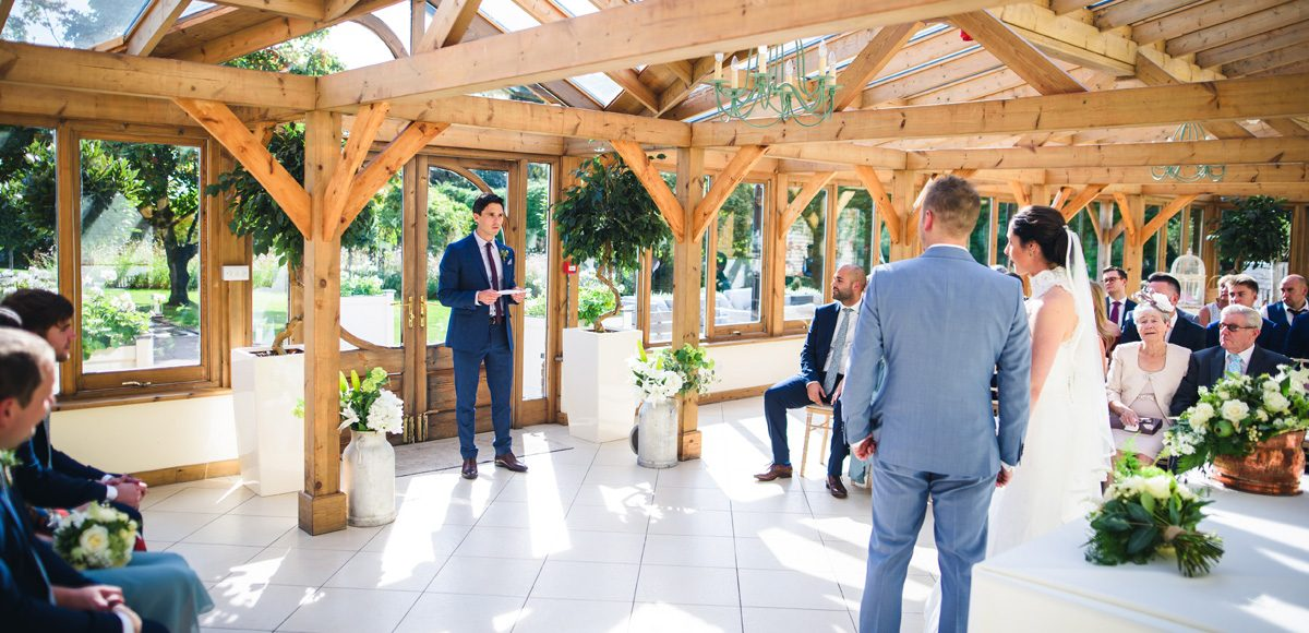 Groomsmen performing a reading to bride and groom during their ceremony at Gaynes Park