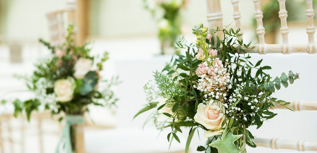 Small bunches of flowers tied to the ceremony chairs