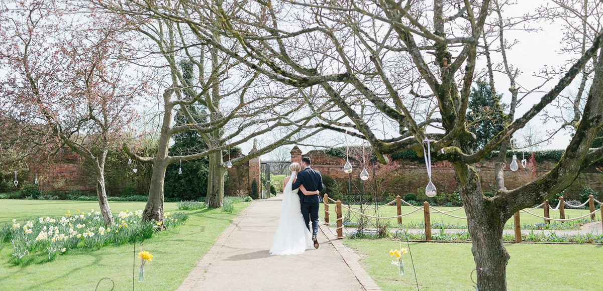 Bride and groom enjoy the Spring time blossoms in the gardens at Gaynes Park wedding venue