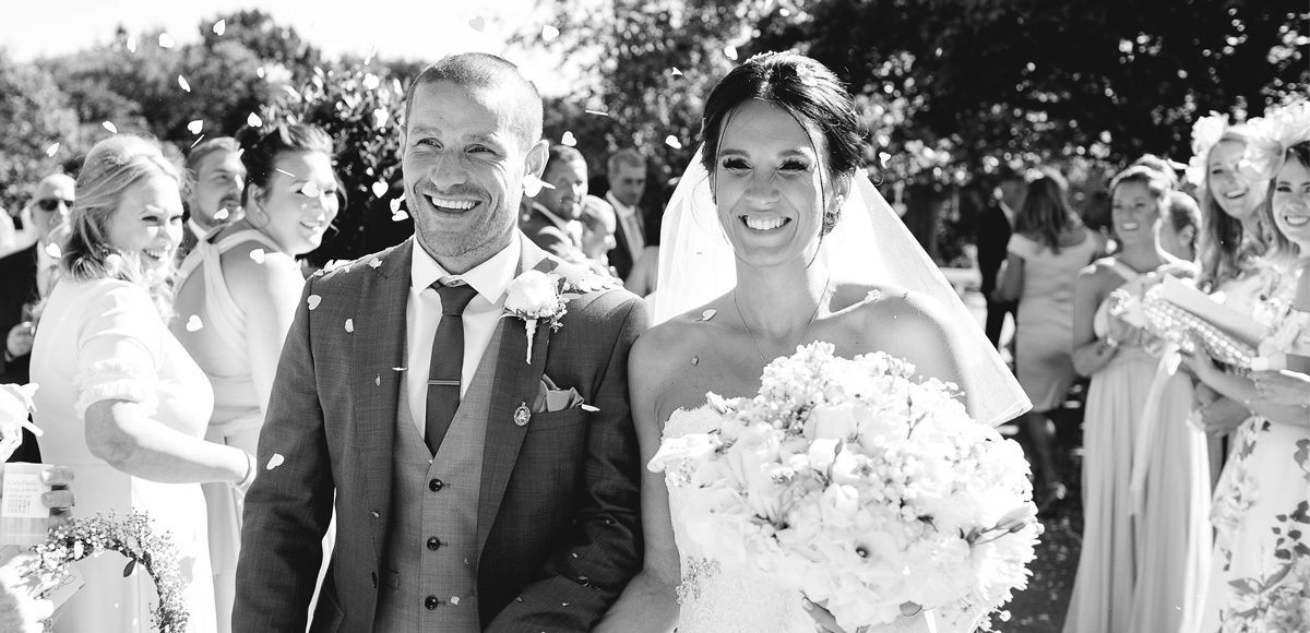 Bride and groom being showered with confetti at Gaynes Park