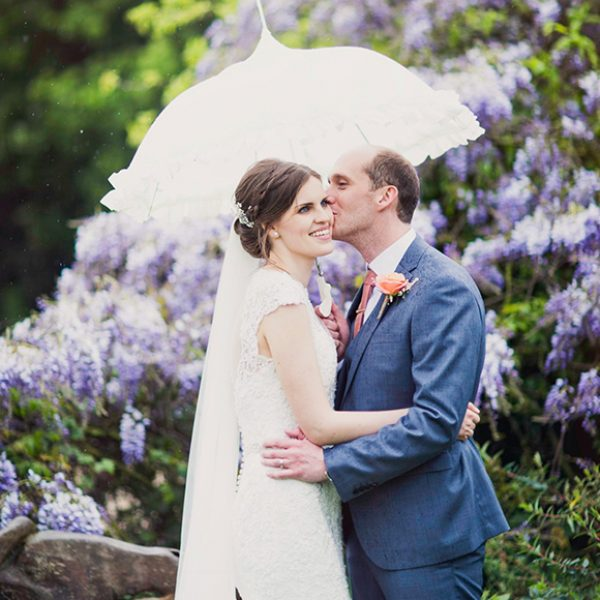 A groom kisses his bride under a white vintage wedding parasol – spring wedding ideas