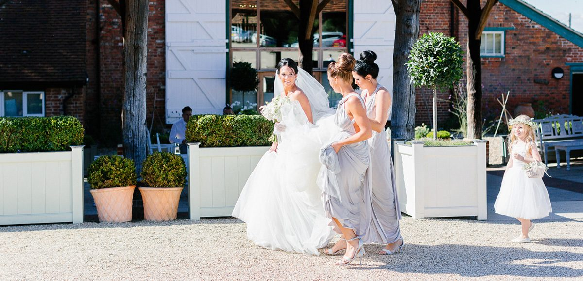 Bridesmaids helping bride with her dress