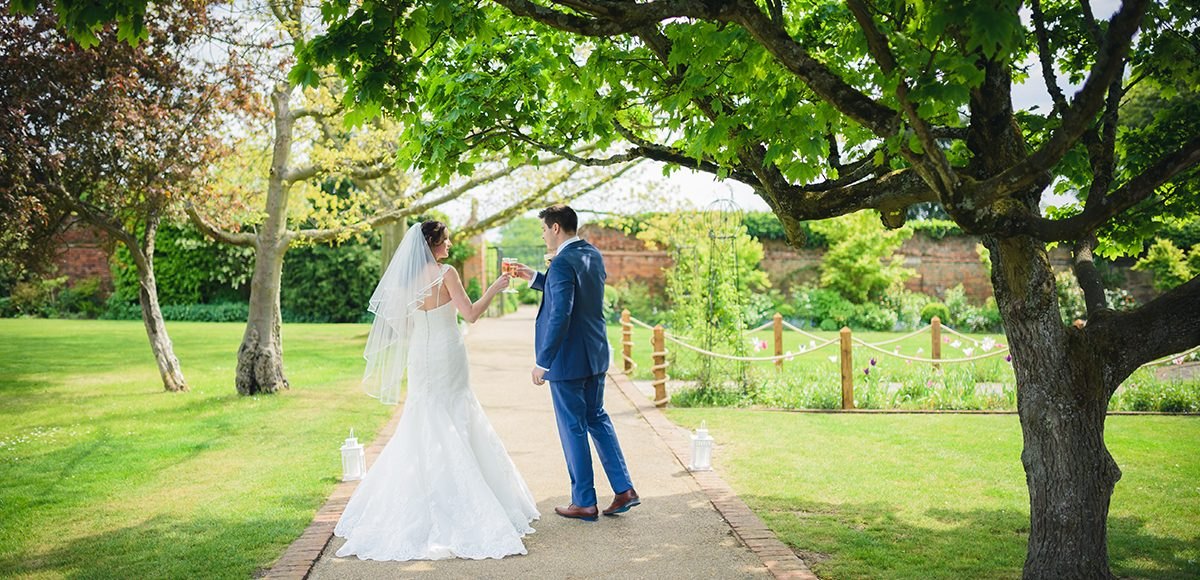 A couple toast to their spring wedding with a glass of champagne in the garden
