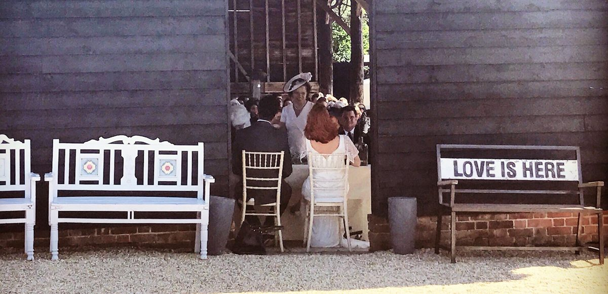A couple sit at the registrar table in the Gather Barn in front of family and friends - outside wedding