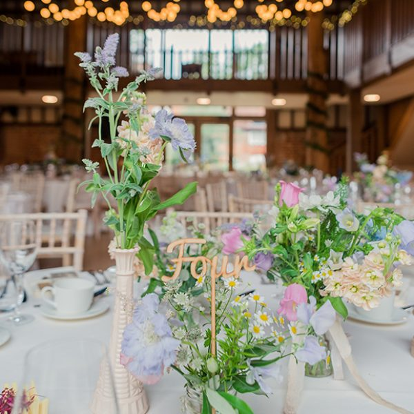 A table is decorated with wedding flowers including daisies, which are perfect for a spring wedding