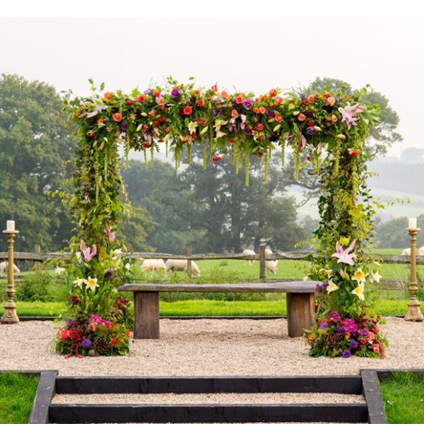 A stunning floral arch stands in the grounds of the beautiful Essex wedding venue and creates a wow factor