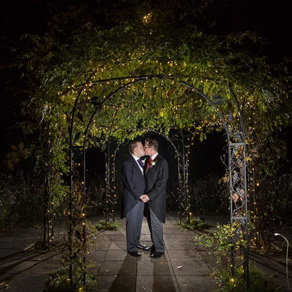 The newlyweds share a kiss under the romantically lit iron pavilion perfect for wedding photos