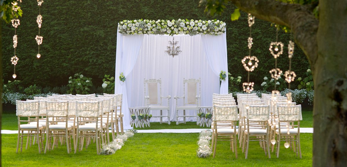Chairs are neatly lined in rows in front of a white canopy for the outside wedding ceremony
