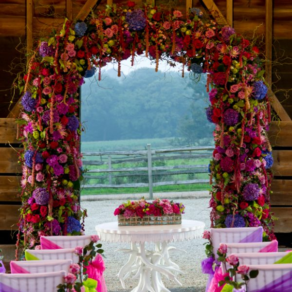 Colour is brought into this outside wedding ceremony with chairs dressed in bright pink and purple chair sashes
