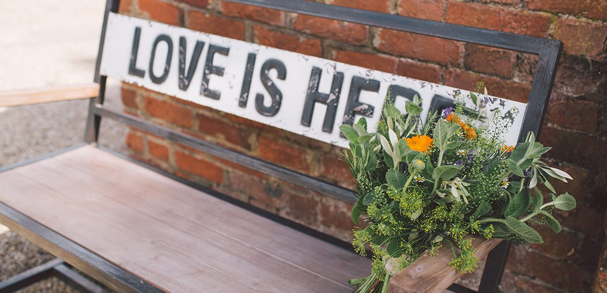 A close up of a wedding bouquet placed on a bench with a sign that reads 'Love is here'