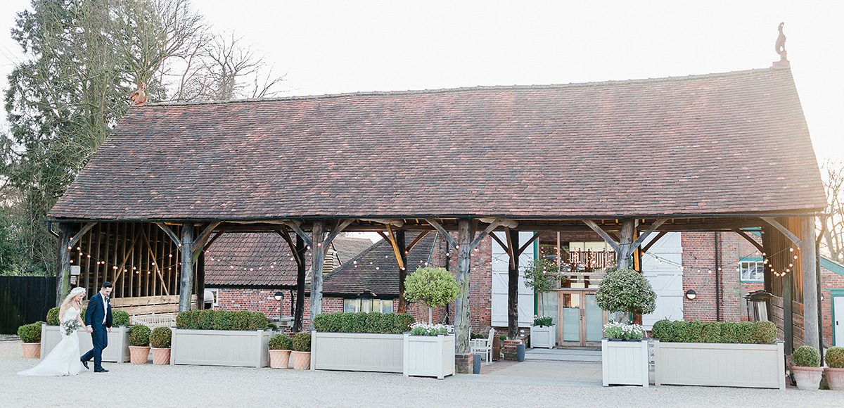 A happy couple stroll hand in hand past the Gather Barn which is perfect for outdoor weddings