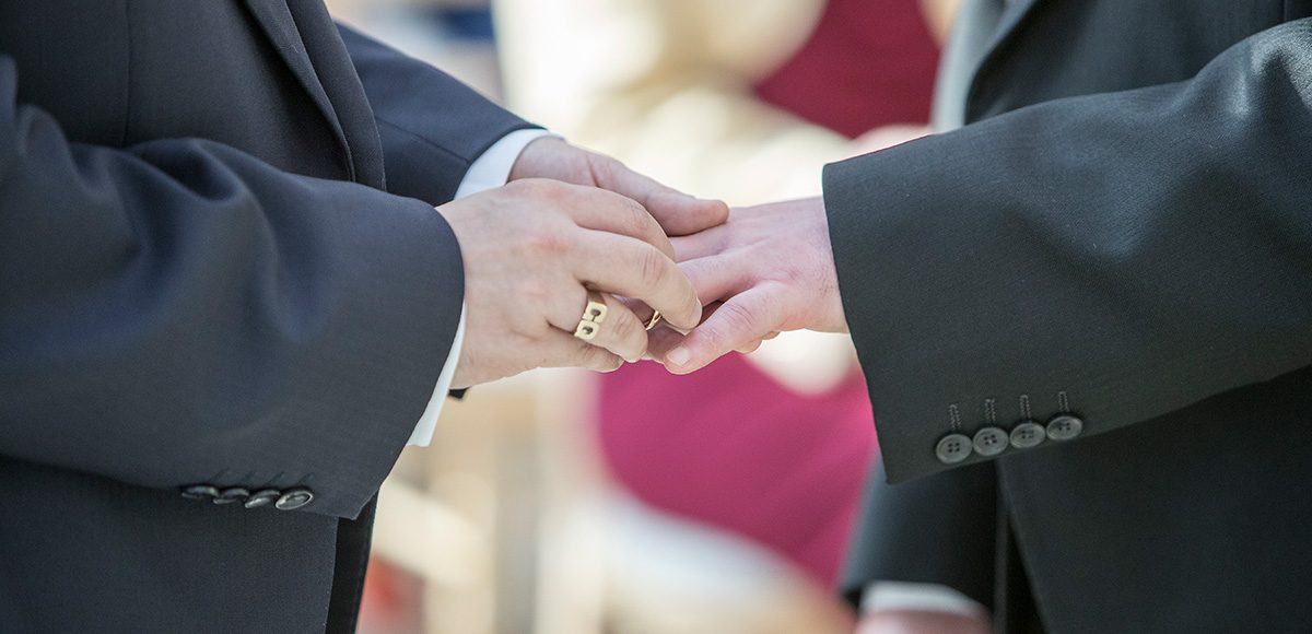 The couple exchange wedding rings during the wedding ceremony at Gaynes Park
