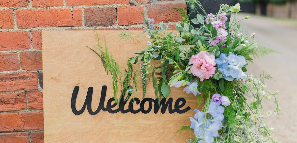 A wooden Welcome sign is decorated with wild flowers for a spring wedding