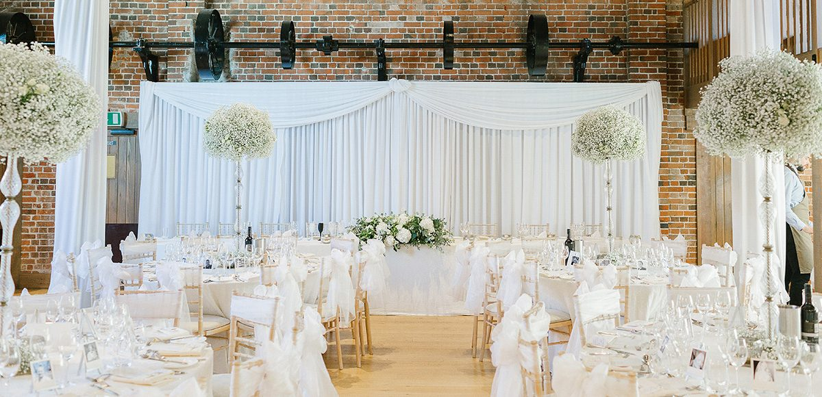 Inside the Mill Barn tables and chairs are covered with white fabric as white drapes hang from the ceiling – white wedding