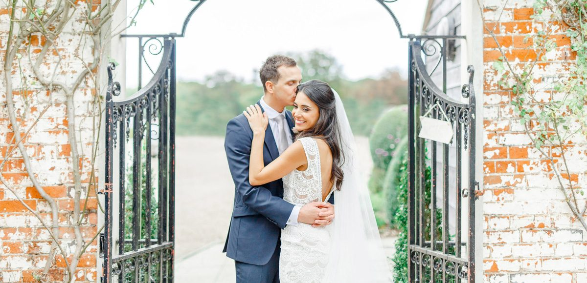 For a stunning wedding photograph the newlyweds stand in front of the gates on The Long Walk at Gaynes Park