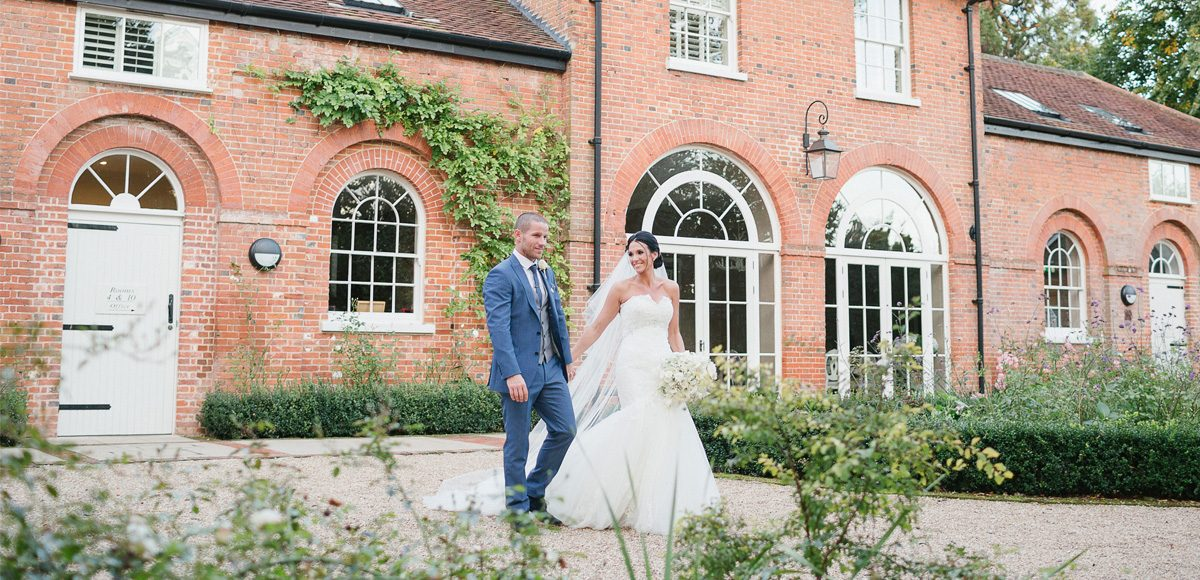 The bride and groom show their happiness as they walk in the gardens in front of the Coach House at Gaynes Park