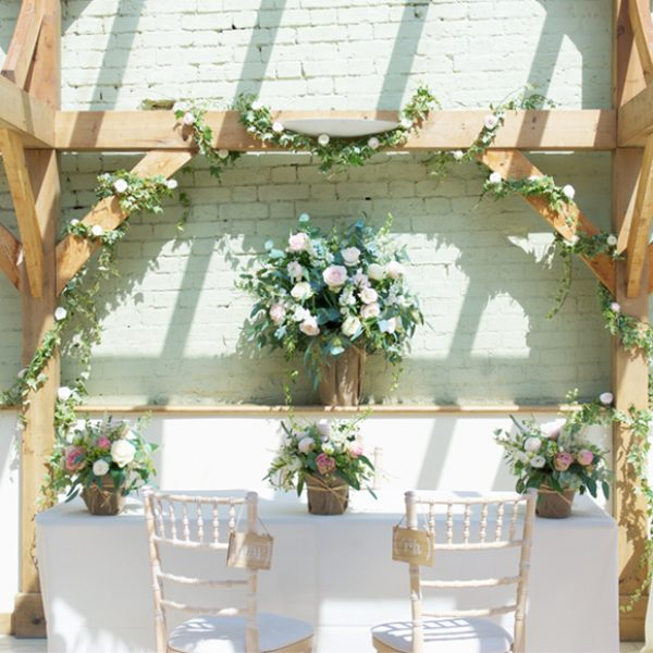 Chairs and beams are decorated with pastel flowers ready for a romantic wedding ceremony in the Orangery at Gaynes Park