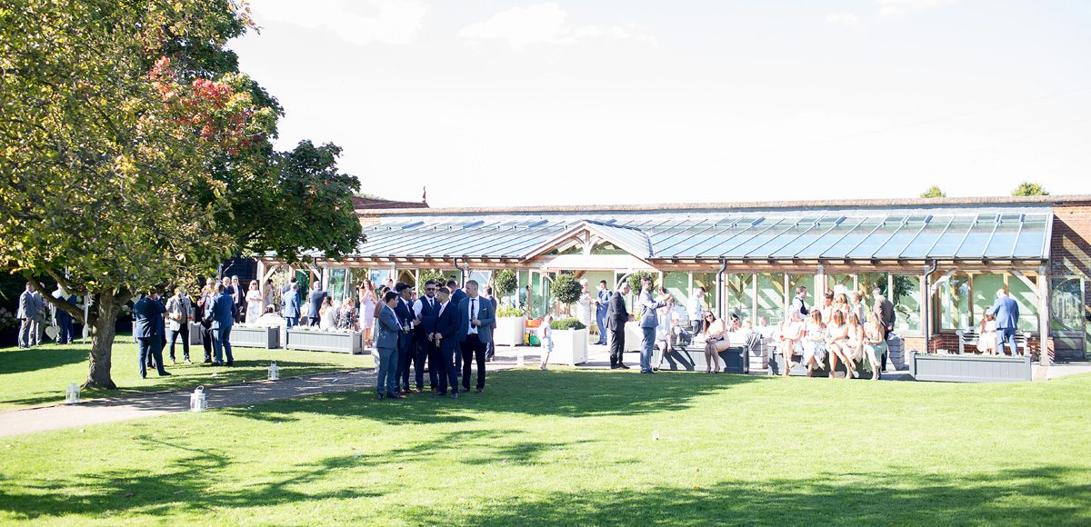 Guests enjoy wedding reception drinks outside the Orangery in the Walled Gardens at Gaynes Park