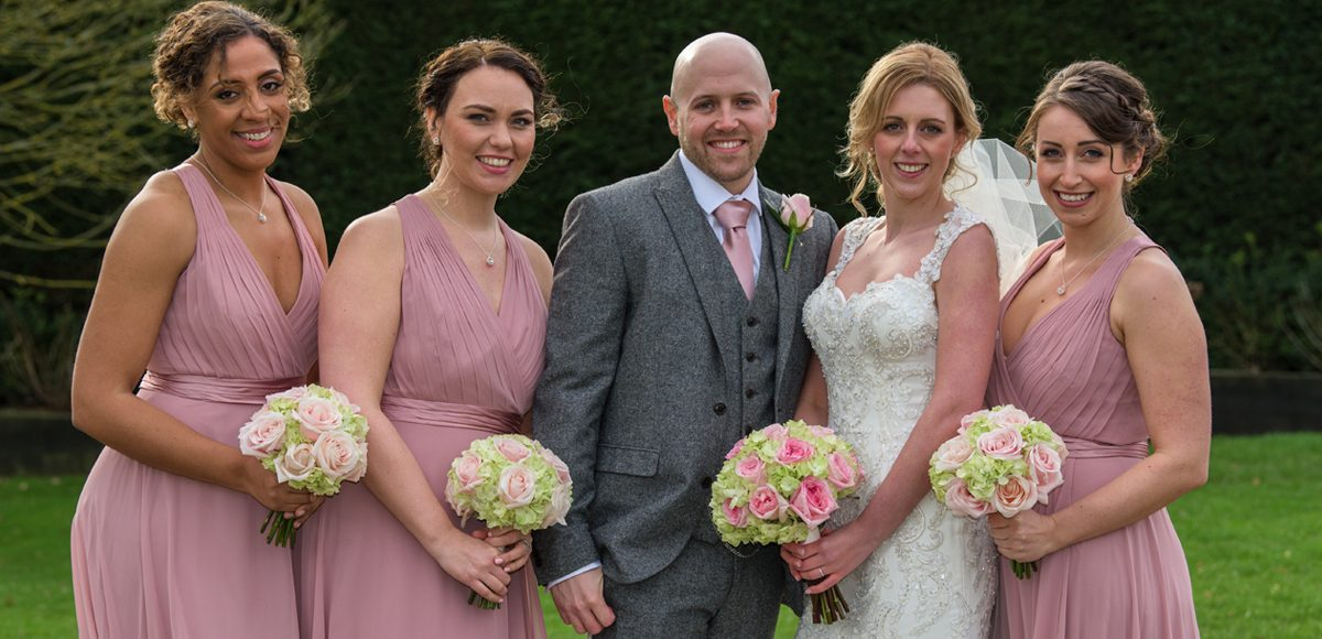 The bridesmaids wear blush pink as they stand with the bride and groom at the Essex wedding venue