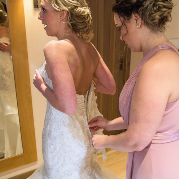 A bridesmaid helps the bride with last minute preparations before the wedding ceremony