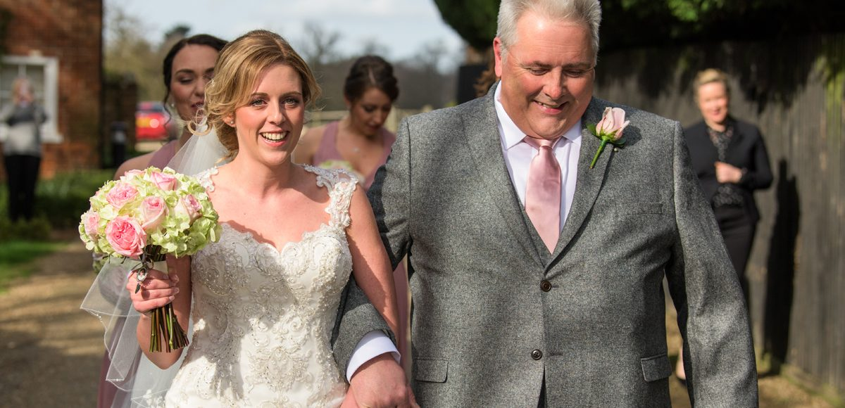 The bride and her father walk towards the wedding ceremony for a spring wedding at Gaynes Park